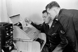 Air Force Sgt. Hohn Bretoski (left) and Army Lt. Col. Charles Fitzgerald (right) during a test of the Cyrillic teleprinters. Copyright AP, 1693-1967.