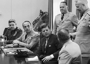 President John F Kennedy amidst his military advisors during the Cuban Missile Crisis in October 1962. Copyright The Daily Banter.